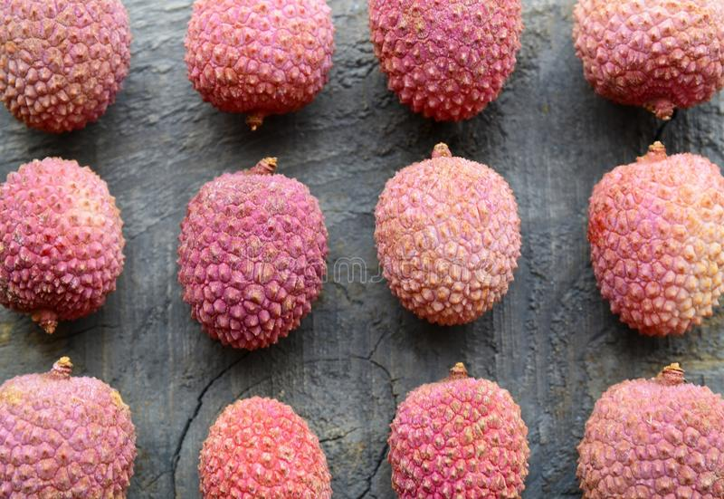 Fresh organic lychees on old wooden background.Exotic tropical lychee fruits pattern.Flat lay,top view. royalty free stock image