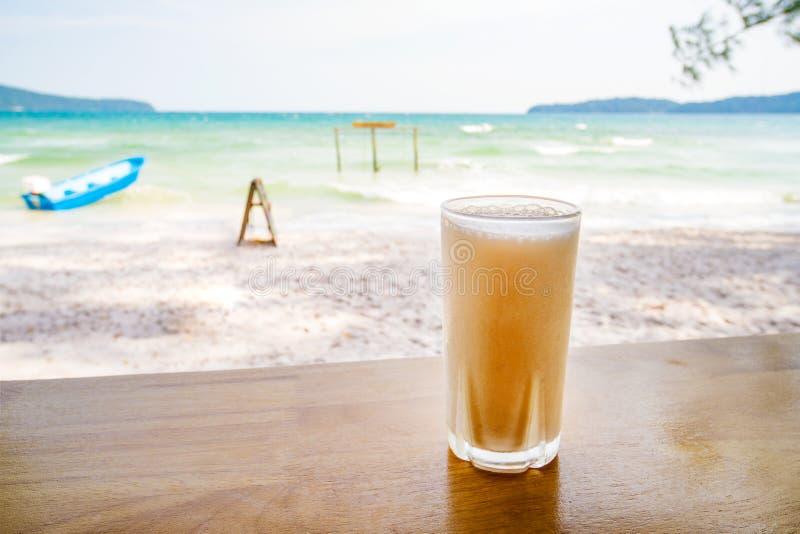 Fresh organic Mango shake in thai restaurant on the beach near sea in island Koh Phangan, Thailand. Glass of cold juice against. Fresh organic Mango or orange royalty free stock photography