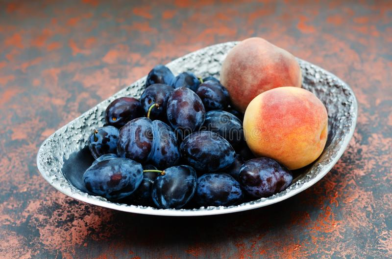 Fresh organic plums and peaches in a metal vase on the bronze shagreen background. Still life of ripe and juicy fruits royalty free stock images