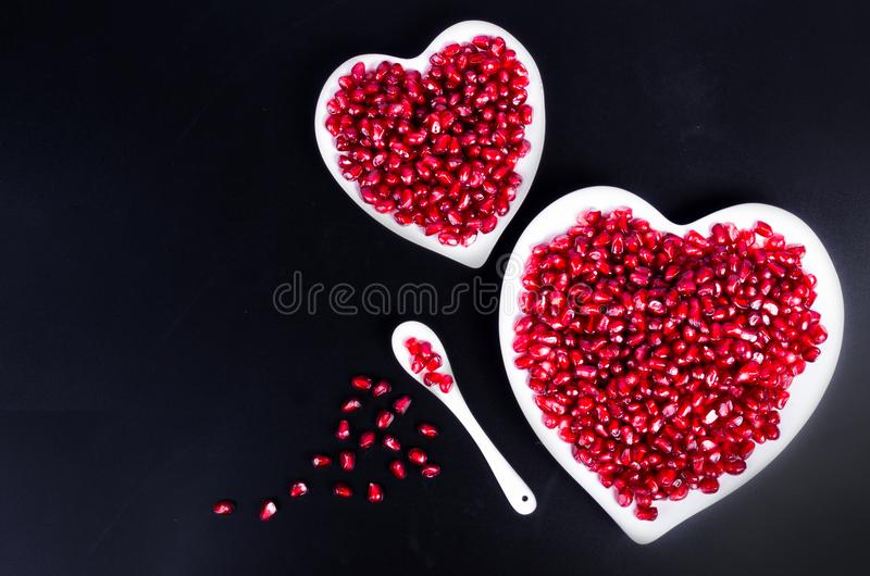Fresh organic pomegranate seeds in white heart shaped bowl. Free space for your text. royalty free stock photography