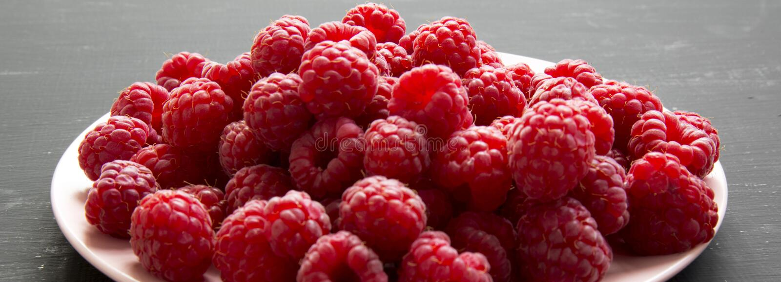 Fresh organic raspberry on a pink plate on black surface, side view. Close-up royalty free stock photography