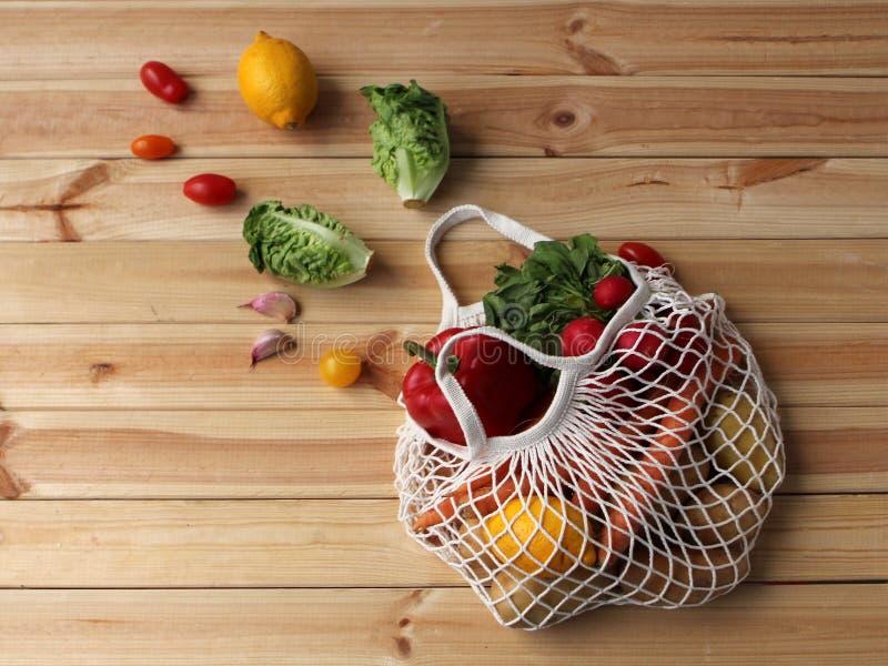 Fresh organic raw carrots, lettuce, paprika, lemons, radishes in a white net bag on a light wooden background stock photos