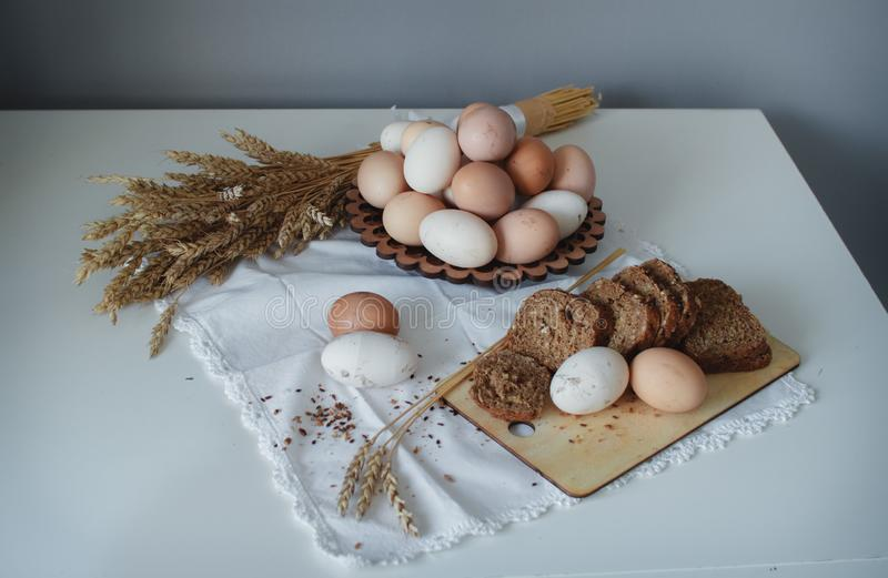 Fresh organic raw chicken brown eggs from the farm and hot grain bread with flax seeds. Healthy diet stock images