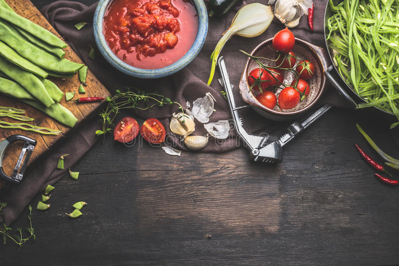 Fresh organic seasonal vegetables on dark rustic wooden background. Tomatoes , Green french beans and cooking ingredients for tas. Ty vegetables dish. Vegan and royalty free stock image