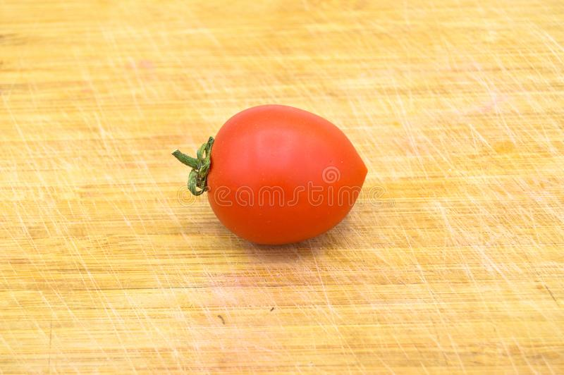 Fresh organic and small one red cherry tomato. Isolated on cutting board stock photography