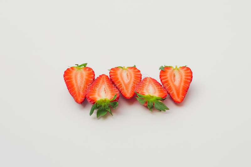 Fresh organic strawberries halved and arranged on a white background. stock photos