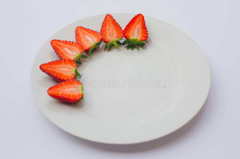 Fresh organic strawberries halved and decorated on a white plate. stock photos