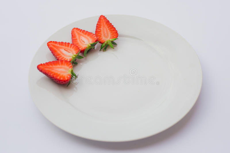 Fresh organic strawberries halved and decorated on a white plate. stock images