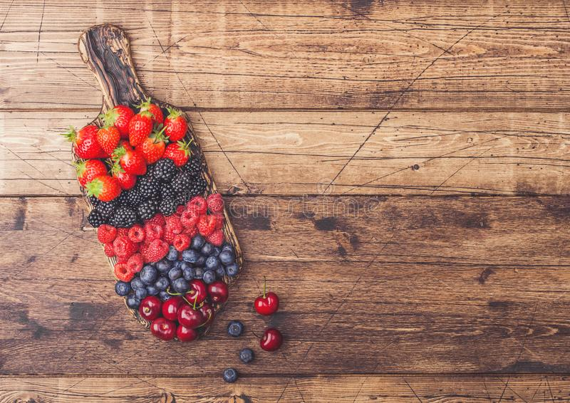 Fresh organic summer berries mix on vintage wooden chopping board on light wooden table background. Raspberries, strawberries, stock image