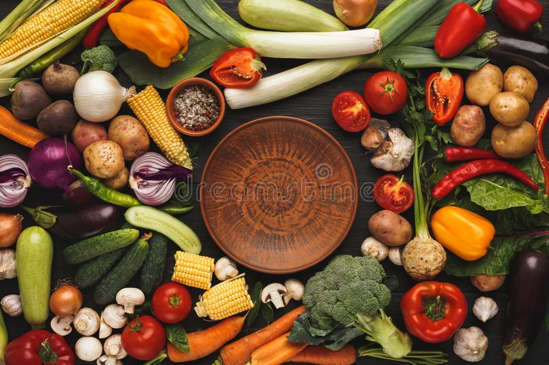 Fresh organic vegetables and brown plate background stock image