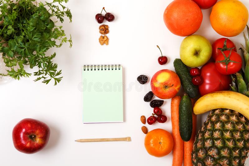 Fresh organic vegetables and fruits, open blank notebook royalty free stock photo