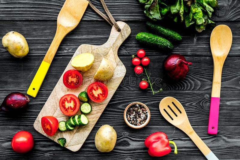 Fresh organic vegetables for healthy food cooking on black wooden background top view stock photo