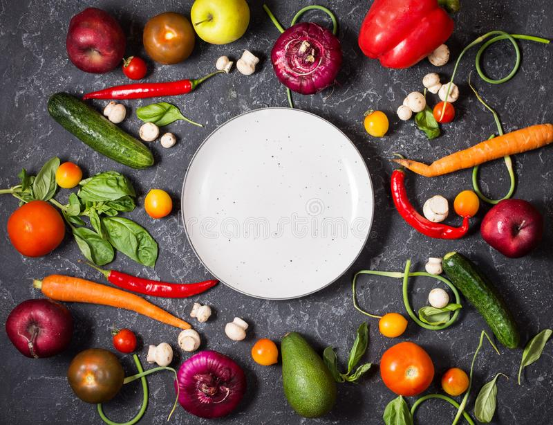 Fresh organic vegetables and seasoning ingredients for tasty vegetarian cooking around plate royalty free stock images