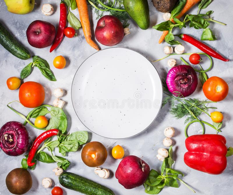 Fresh organic vegetables and seasoning ingredients for tasty vegetarian cooking around plate stock images