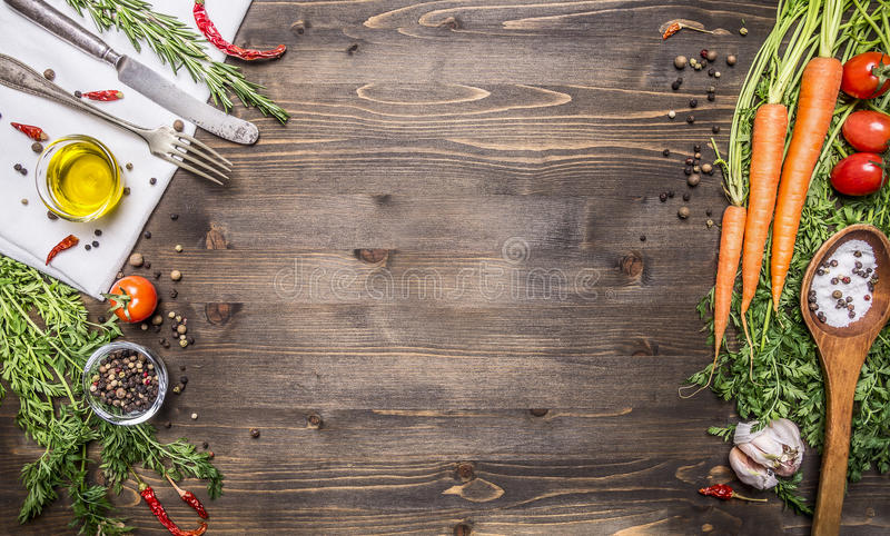 Fresh organic vegetables and spoons on rustic wooden background, top view, border. Healthy food or vegetarian cooking concept royalty free stock images