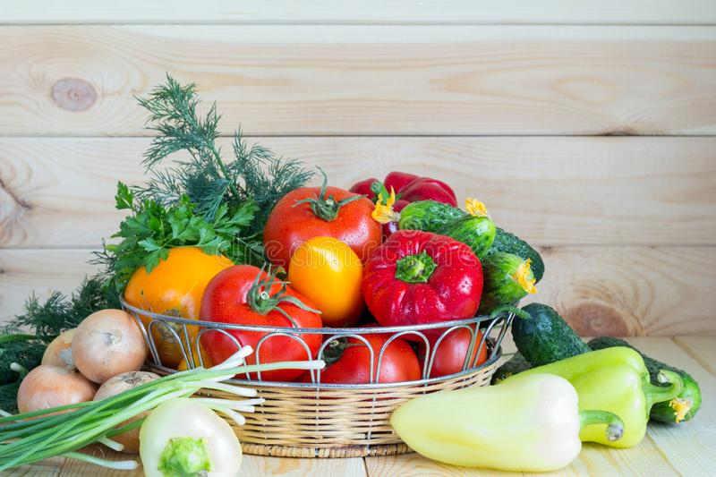 Fresh organic vegetables in wicker basket on wooden table with copy space. Summer harvest concept. royalty free stock images