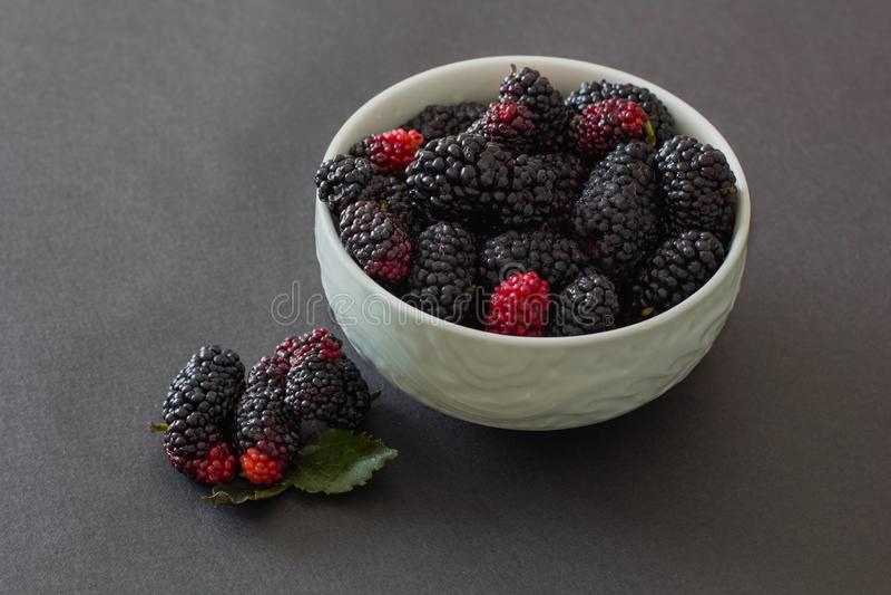 Fresh organic vietnamese black mulberry on grey background in green bowl stock photo