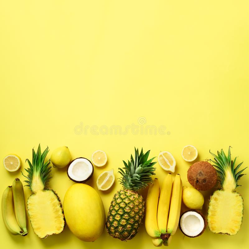 Fresh organic yellow fruits over sunny background. Monochrome concept with banana, coconut, pineapple, lemon, melon. Top royalty free stock image