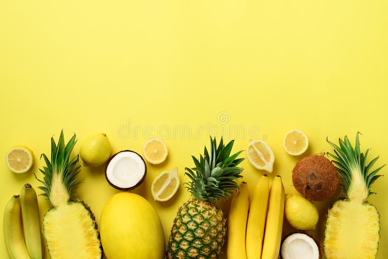 Fresh organic yellow fruits over sunny background. Monochrome concept with banana, coconut, pineapple, lemon, melon. Top. View. Copy space. Pop art design royalty free stock image