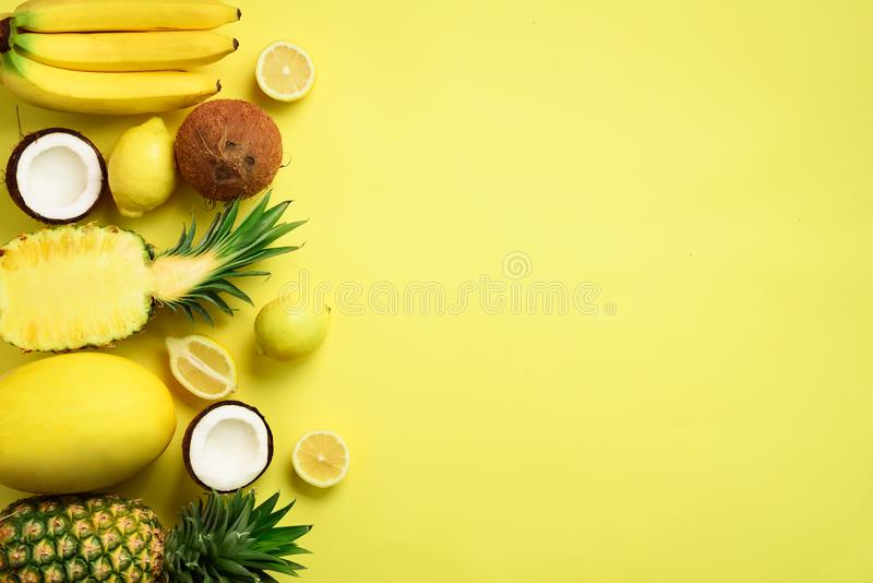 Fresh organic yellow fruits over sunny background. Monochrome concept with banana, coconut, pineapple, lemon, melon. Top. View. Copy space. Pop art design royalty free stock photo