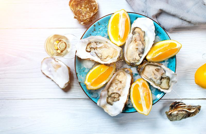 Fresh oysters close-up on blue plate, served table with oysters, lemon and champagne in restaurant. Gourmet food. Tabletop view stock photo