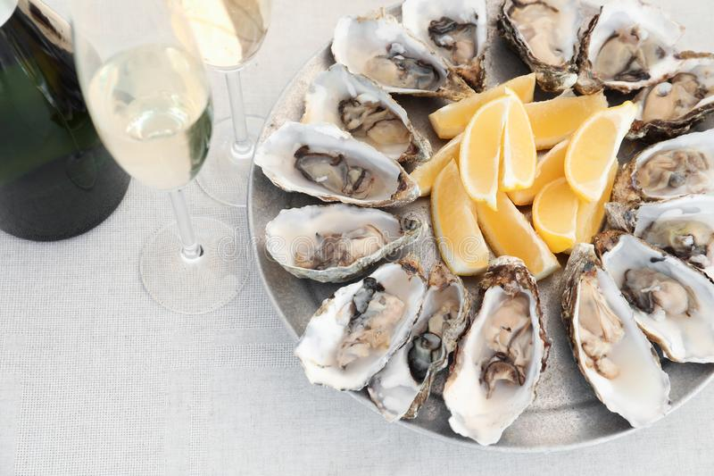 Fresh oysters with cut juicy lemon served royalty free stock photography