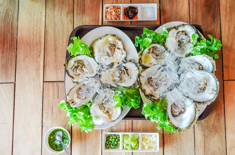 Fresh oysters on ice served with lime and grilled onion in a restaurant, seafood menu design, Thai style, top view stock photos