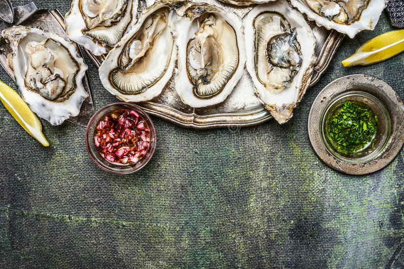 Fresh oysters with lemon and various sauces on rustic background, top view, place for text stock image
