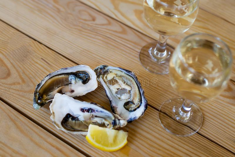 Oysters with slice of lemon, two glasses of wine royalty free stock images