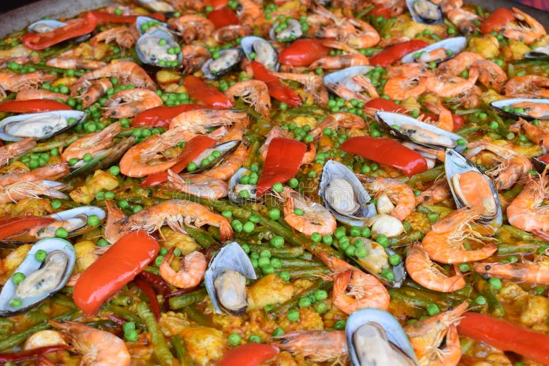 Fresh paella – a rice dish with vegetables and fresh seafood- on a food market royalty free stock images