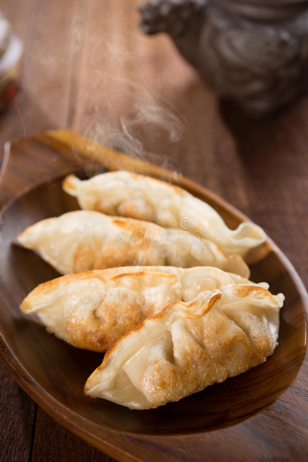Fresh pan fried dumplings. On plate with hot steams. Asian food on rustic old vintage wooden background royalty free stock photos