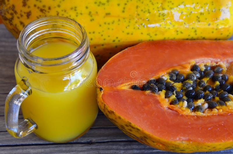 Fresh papaya juice in a glass jar ripe papaya fruit on old wooden table.Healthy drink,detox,diet or vegan food concept. stock images