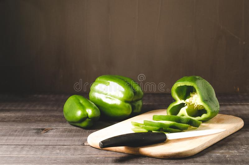 fresh paprika cut on a wooden board on a dark background/green pepper paprika cut on a wooden board, selective focus royalty free stock photo