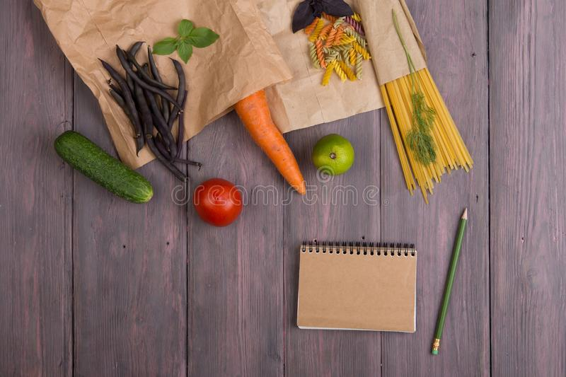 Fresh pasta ingredients in eco paper bags - spaghetti pasta, carrot, basil, tomato and other vegetables, notepad for recipe royalty free stock photo