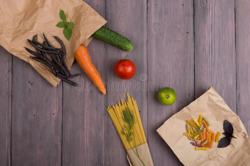 Fresh pasta ingredients in eco paper bags - spaghetti pasta, carrot, basil, tomato and other vegetables stock image