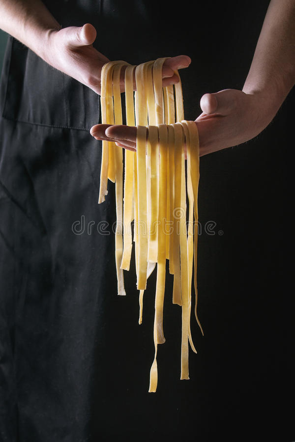 Free Fresh Pasta Tagliatelle In Man`s Hands Stock Image - 87514941