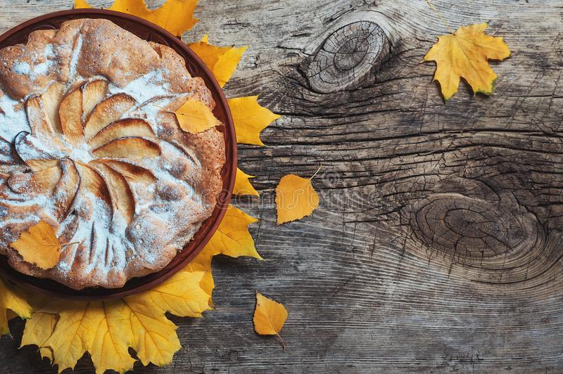 Fresh pastry apple pie charlotte on wooden table background decorated with yellow autumn leaves. Fall Food Cook Cuisine Homemade stock photo