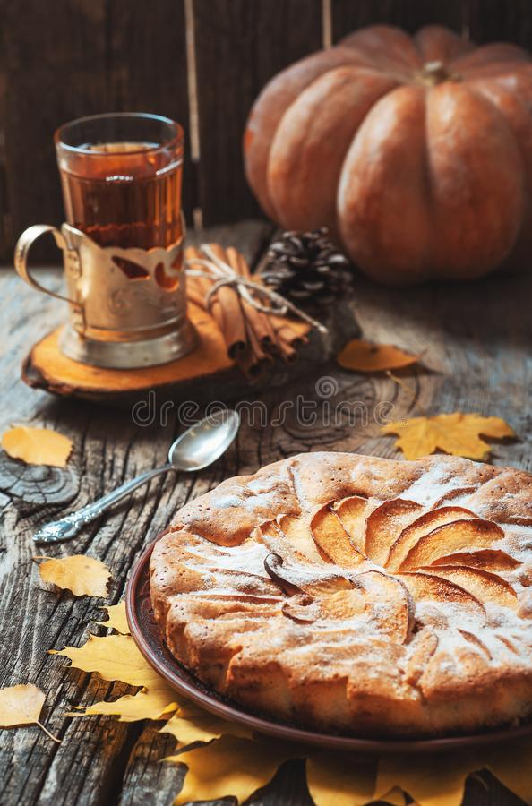 Fresh pastry apple pie with sugar powder on wooden table with hot drink tea and cinnamon on background. Homemade cake Thanksgiving stock images