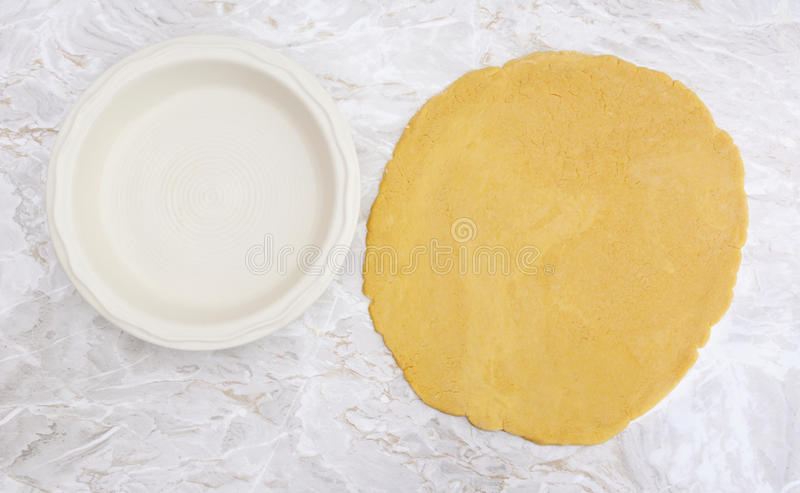 Fresh pastry rolled out in a circle to line pie dish stock photography