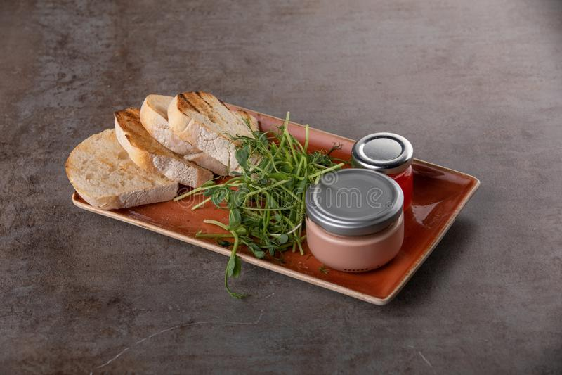 Fresh pate in glass jar with toasted bread on grey table stock images