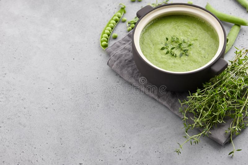 Fresh pea soup with thyme in ceramic pot. Fresh green pea soup served in bowl with thyme on gray concrete background, copy space stock photography