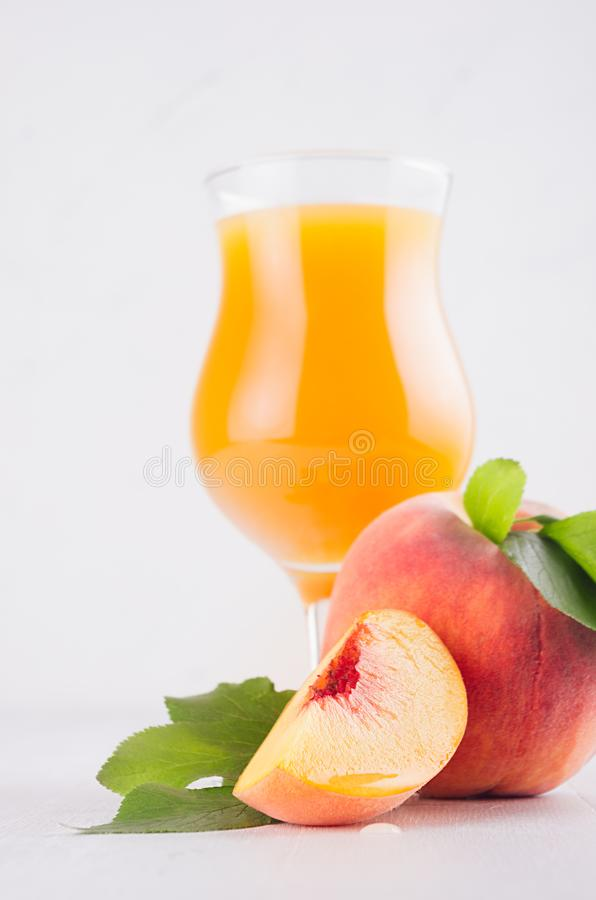 Fresh peach juice in glass with whole peach, ripe juicy slice and green leaves in white modern kitchen interior, closeup. stock images
