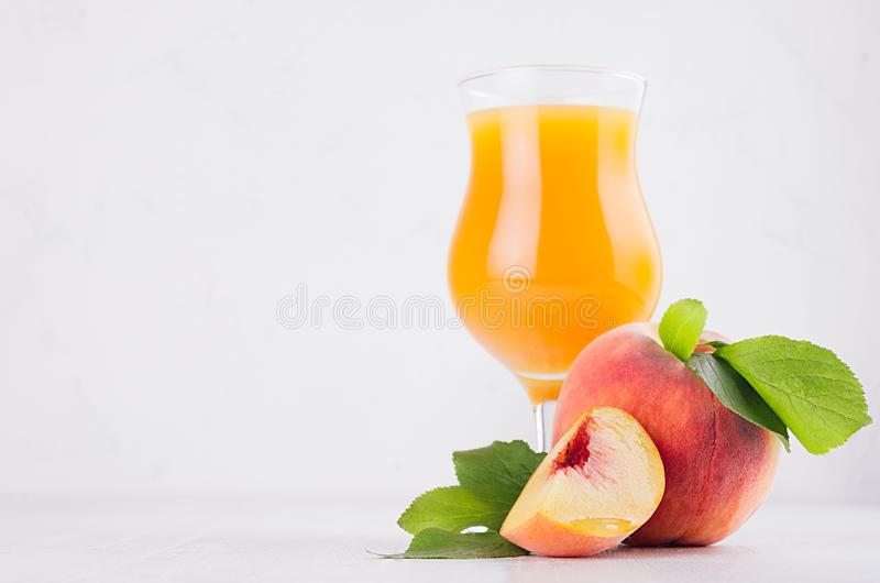 Fresh peach juice in glass with whole peach, ripe juicy slice and green leaves in white modern kitchen interior. stock photo