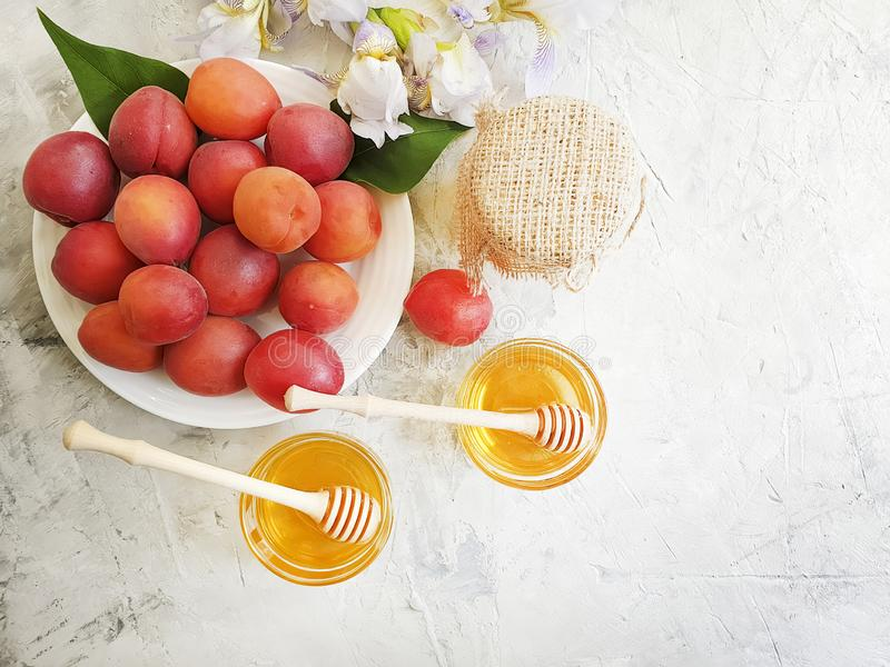 Fresh peach on a plate, honey, iris flower on a gray concrete background. Delicious royalty free stock photos