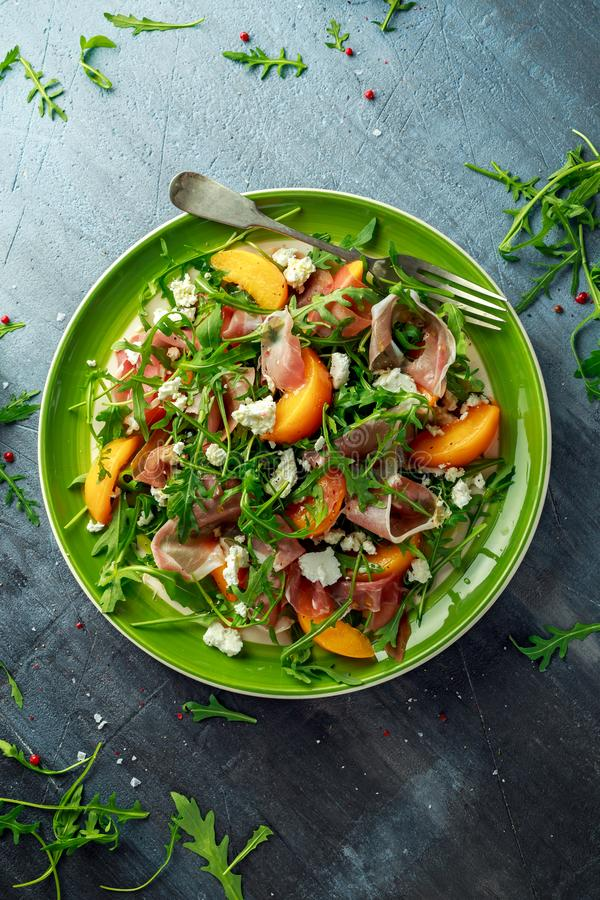Fresh Peach salad with Parma ham, feta cheese and vegetables in a green plate. healthy food royalty free stock photos