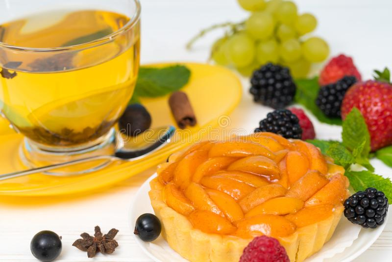 Fresh peach tart with spicy lemon tea royalty free stock image