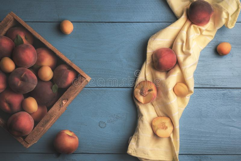 Fresh peaches and apricots in wooden box stock image