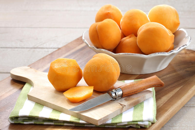 Fresh peaches in a bowel. Fresh delicious yellow peaches in an antique white bowel on wooden board with some peeled peaches in the fore ground royalty free stock photo