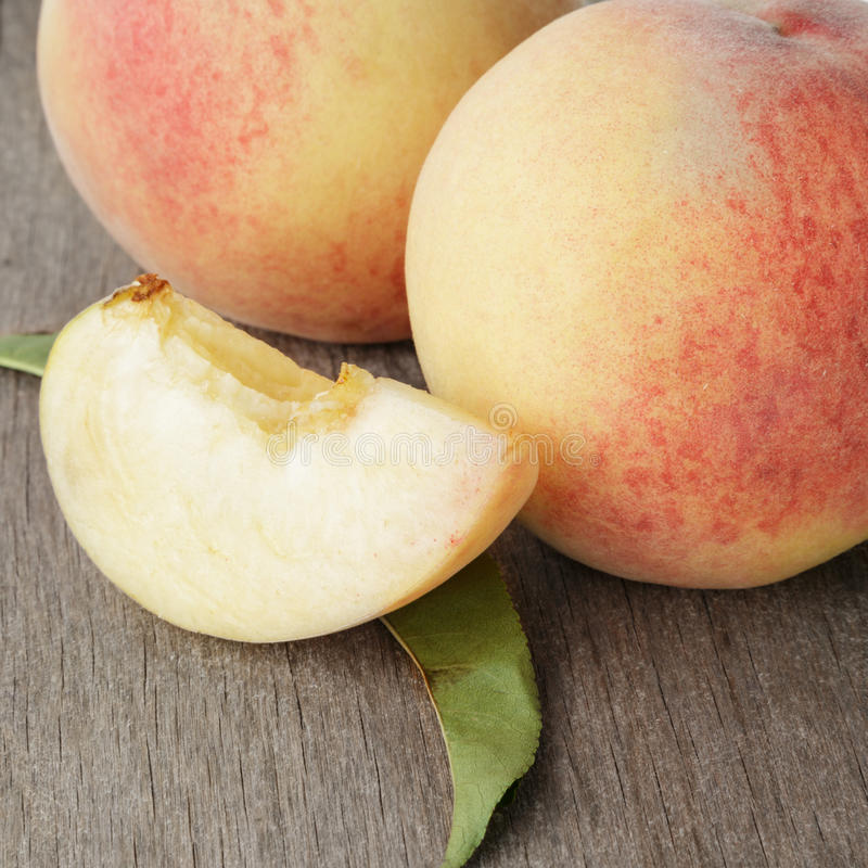 Fresh peaches with lobule. On old wooden table stock images
