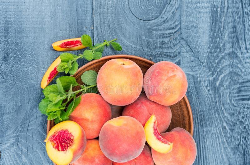 Fresh peaches with mint on a wooden background. Close-up stock photo